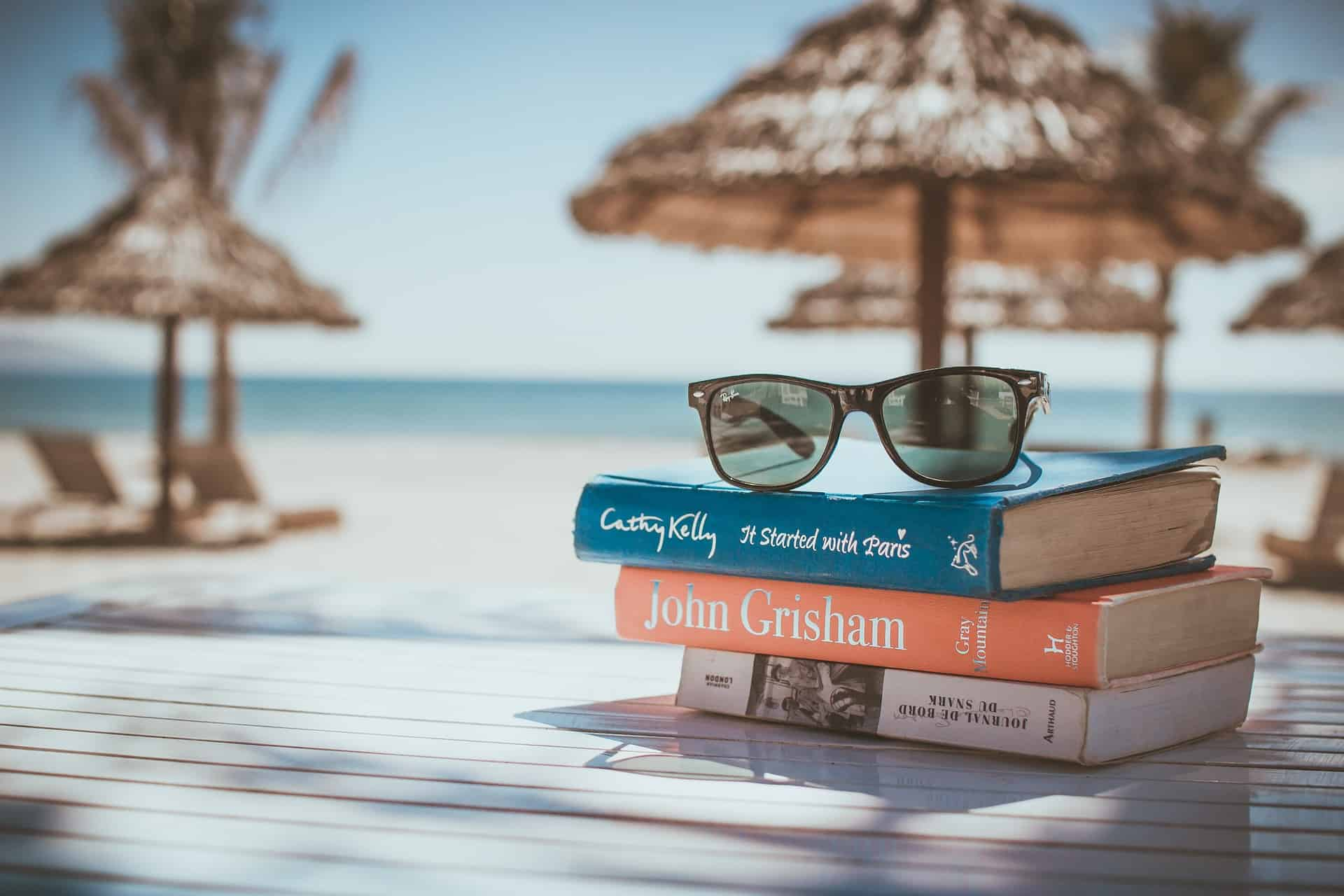 tropical vacation with books and sunglasses