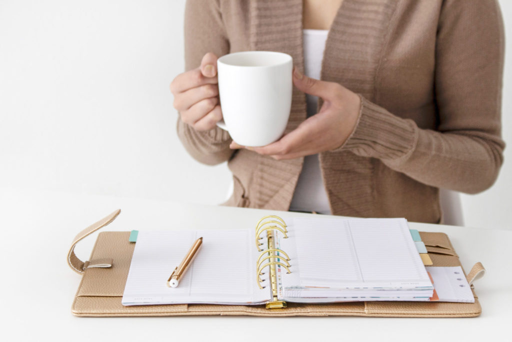 Woman goal setting while drinking coffee